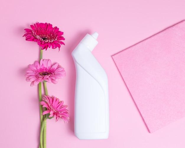 ピンクの背景に洗浄剤、洗浄布、ガーベラの花と白いプラスチックボトル
