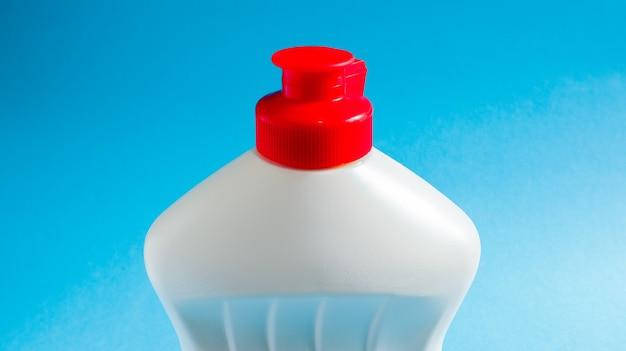 파란색 배경에 세제, 표백제 또는 섬유 유연제가 있는 흰색 플라스틱 병. 액체 세척 분말. 청소의 개념입니다.