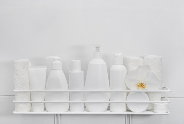 White plastic bottles of beauty care products on bath shelf