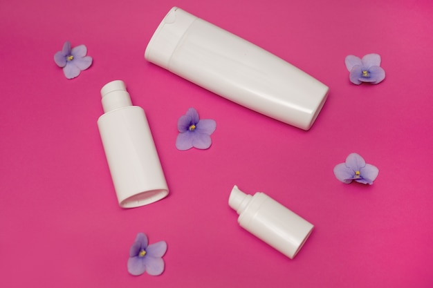 White plastic bottles on pink background, set of cosmetic containers with dispenser. copy space, empty place for text. toiletries, pump lotion. moisturizing cream for body, face. concept of skin care
