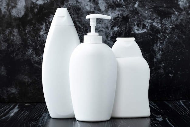 White plastic bottles of shampoo, antibacterial liquid soap and shower gel on black marble background in bathroom. concept of hygiene, disinfection. protection of flu virus, influenza.