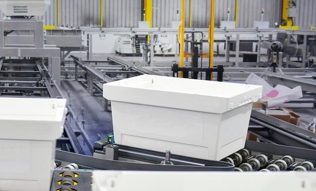 Белая пластиковая коробка на концепции системы транспортировки посылок конвейерной ленты