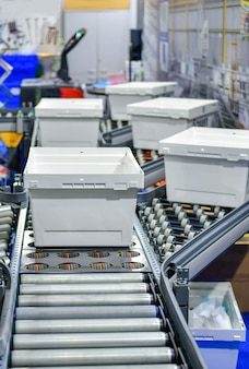 Белые пластиковые ящики на конвейерной ленте. концепция системы транспортировки посылок