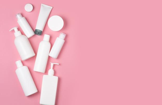 Белые пластиковые банки на розовом фоне. косметика по уходу за кожей. средства для мытья, дезинфекции и стирки.