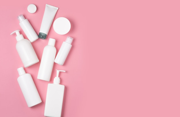 White plastic cans on a pink background. cosmetics for skin care. means for washing, disinfecting and washing.