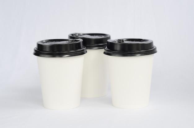 白の上の黒い帽子が付いている白いプラスチック製のコーヒーカップ