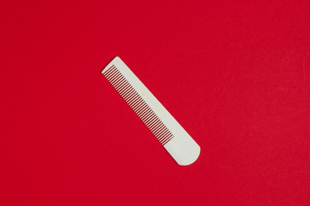 赤に白いプラスチック製の櫛。ヘアケア、美容コンセプト。上面図