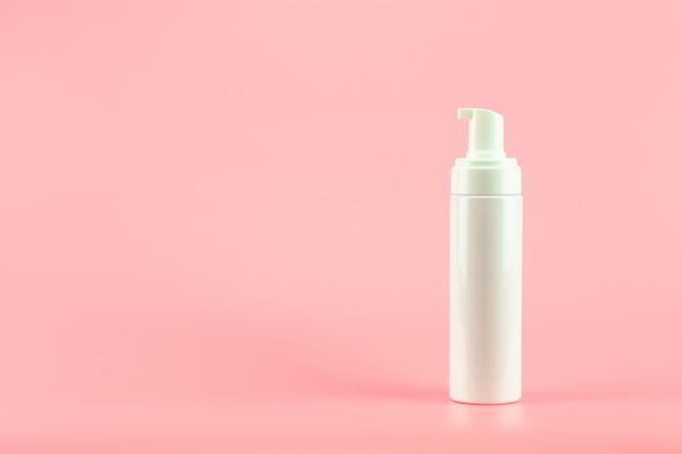 ピンクの背景に白いプラスチック化粧品ローションボトル。