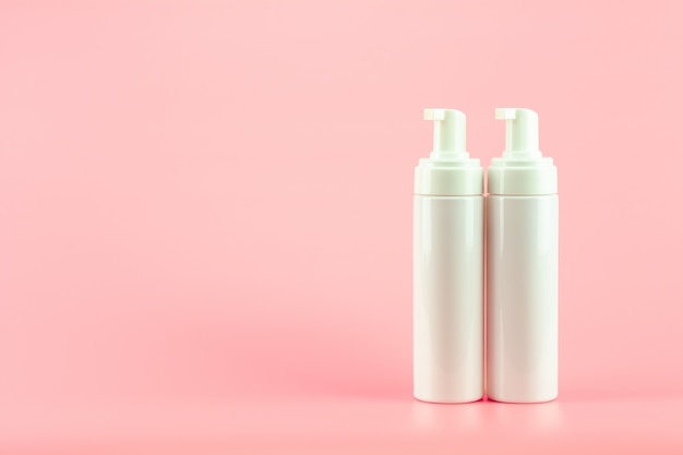 White plastic cosmetic lotion bottle on pink background.