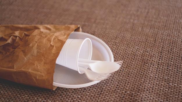ベージュの背景に紙のパケットの白いプラスチック皿。プラスチックとエコロジーのリサイクルの概念