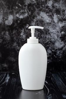 White plastic dispenser bottle with liquid soap on black marble wall. hygiene concept.