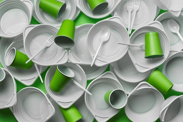 White plastic disposable tableware on green background