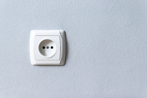 White plastic euro socket on gray wall with copyspace