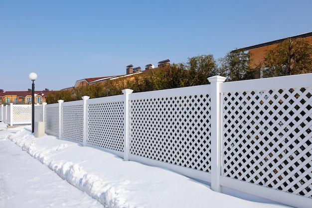 맑은 겨울날 현대 코티지 마을에 있는 흰색 플라스틱 울타리