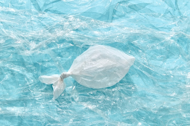 Белая пластиковая рыба на прозрачном полиэтилене с копией пространства. экологическая проблема загрязнения окружающей среды океана.