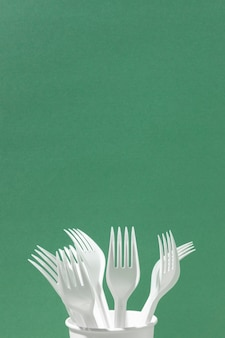 Forchette di plastica bianche in uno spazio della copia della tazza