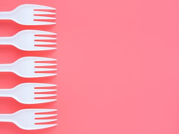ピンクの背景、上面図、フラットレイの白いプラスチックフォーク。