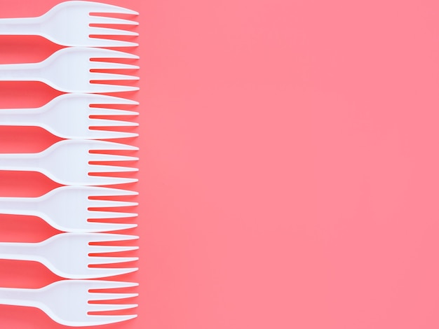 White plastic forks on a pink background, top view, flat lay