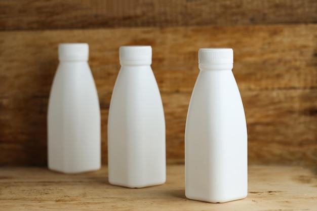 White plastic milk bottles on retro wooden table background