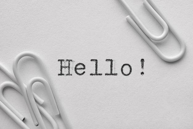 Белые пластиковые скрепки со словом hello напечатаны на пишущей машинке