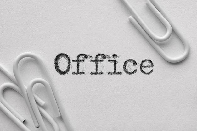 Белые пластиковые скрепки с офисным словом, напечатанным пишущей машинкой