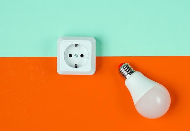 파란색 주황색 배경에 흰색 플라스틱 전원 소켓 및 led 전구. 미니멀리즘. 평면도