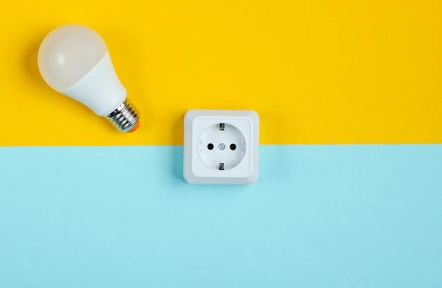白いプラスチックの電源ソケットと青黄色のテーブルにled電球。ミニマリズム。上面図