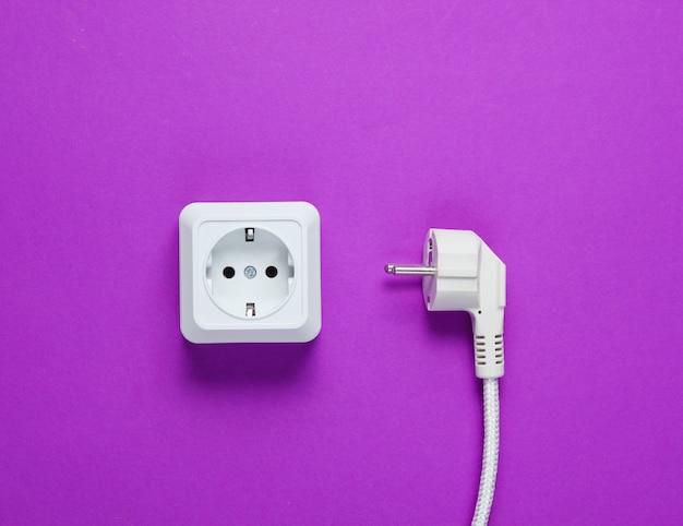 白いプラスチック製の電源ソケットと紫色のテーブルの電源プラグ。上面図