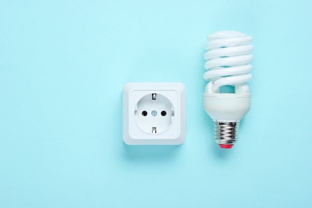 白いプラスチックの電源ソケットとスパイラル電球。ミニマリズム。上面図
