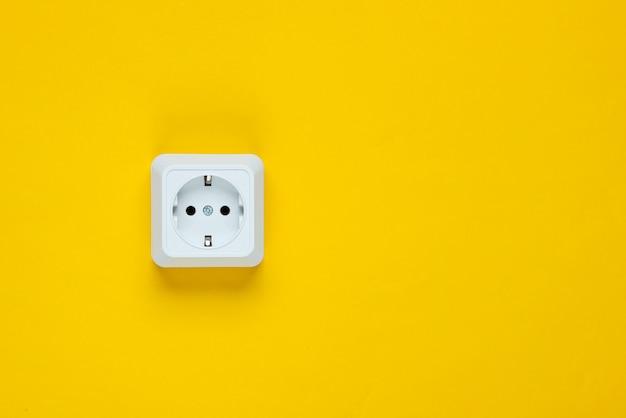 노란색 테이블에 흰색 플라스틱 전원 소켓입니다. 복사 공간 벽. 미니멀리즘