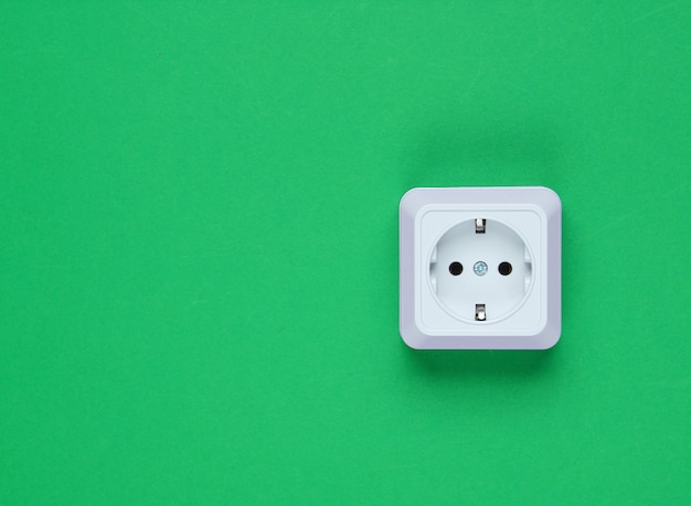 녹색 배경에 흰색 플라스틱 전원 소켓입니다. 복사 공간 벽. 미니멀리즘