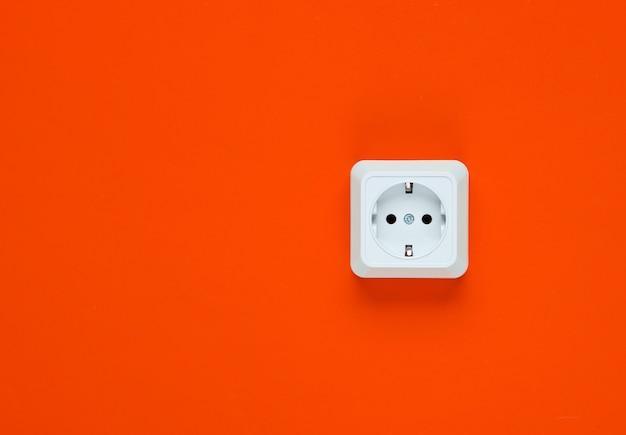 주황색 배경에 흰색 플라스틱 전원 소켓입니다. 복사 공간 벽. 미니멀리즘
