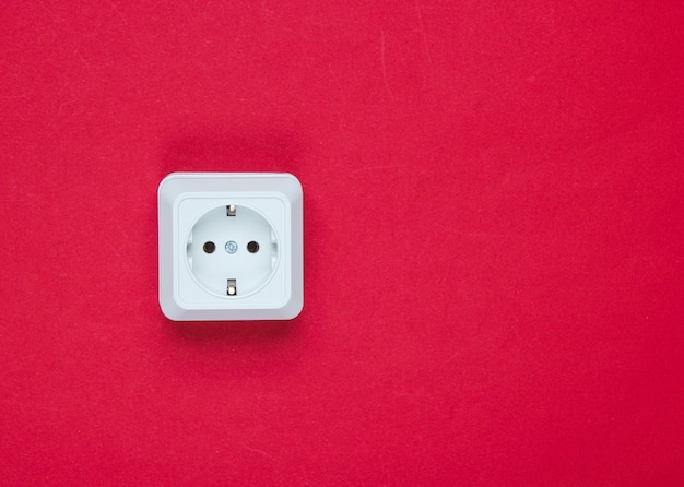 빨간 테이블에 흰색 플라스틱 전원 소켓입니다. 복사 공간 벽. 미니멀리즘