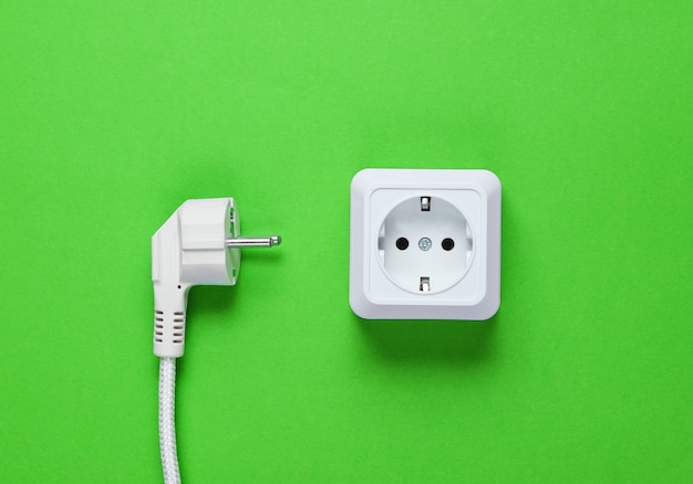 White plastic power socket and power plug on green background. top view