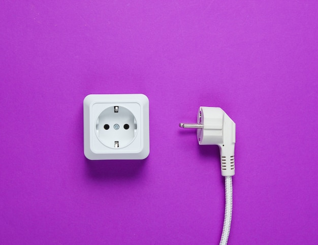 White plastic power socket and power plug on purple table. top view