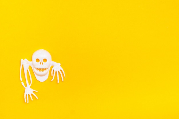 White plastic skull with bones on a yellow cardboard background. ready halloween illustration. copy space