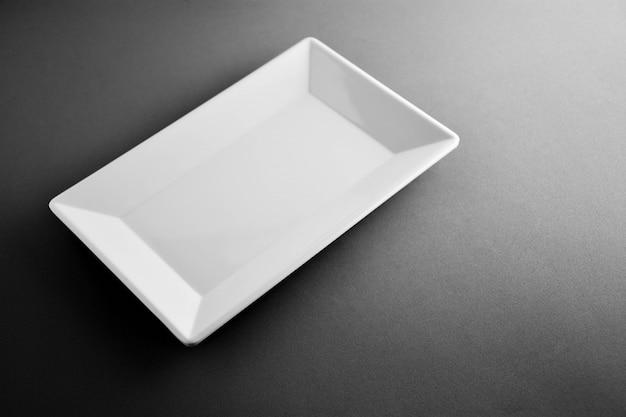 White plastic square dish on black desk