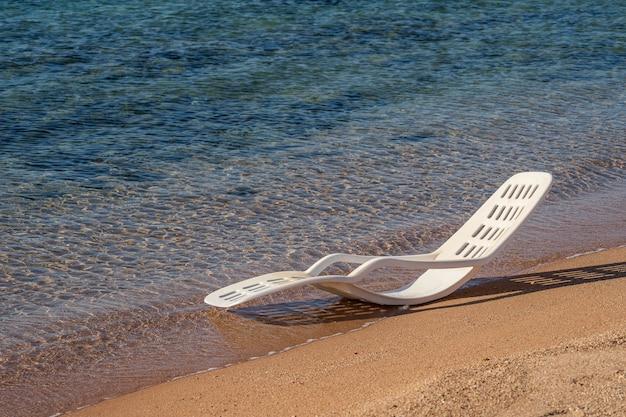 Белый пластиковый шезлонг в морской воде на тропическом пляже в шарм-эль-шейхе, египет