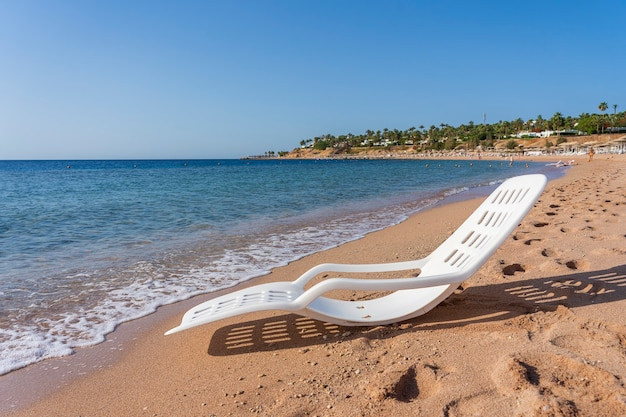 Белый пластиковый шезлонг возле морской воды на тропическом пляже в шарм-эль-шейхе, египет. концепция путешествия и природы