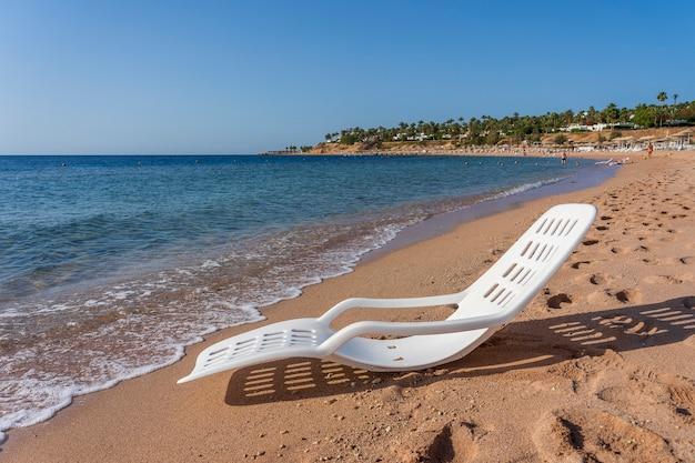 이집트 샤름 엘 셰이크의 열대 해변에 있는 바닷물 근처에 있는 흰색 플라스틱 일광욕용 의자. 여행과 자연 개념