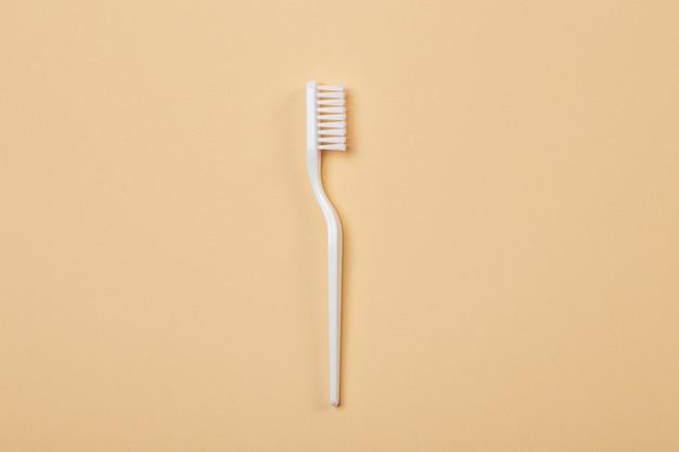 Белая пластиковая зубная щетка на бежевом фоне