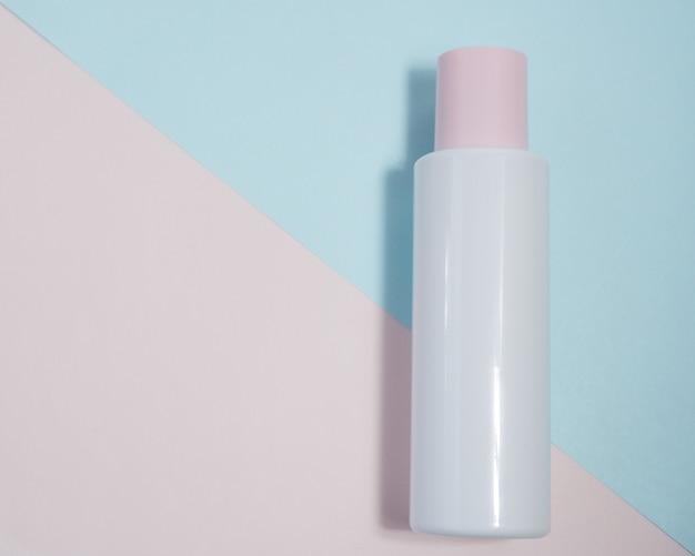 Белая пластиковая трубка контейнер с розовой крышкой для ухода за кожей на розово-синем фоне с копией пространства