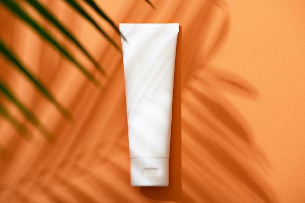 야자수 잎과 그림자가 있는 주황색 배경에 얼굴, 손, 바디 크림이 있는 흰색 플라스틱 튜브. 자외선 차단제, 자외선 차단제. spf 플랫 레이와 여름 스킨 케어 개념. 모형.