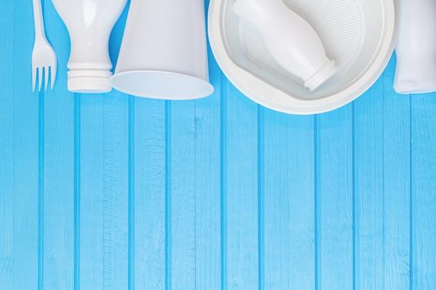 Белые пластиковые отходы для переработки на синем фоне с копией пространства