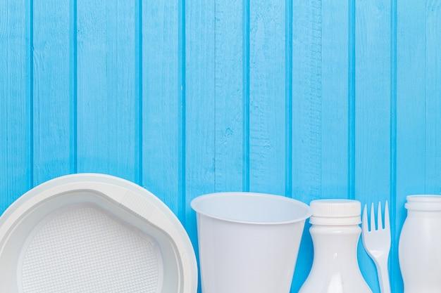 青い背景にリサイクルするための白いプラスチック廃棄物