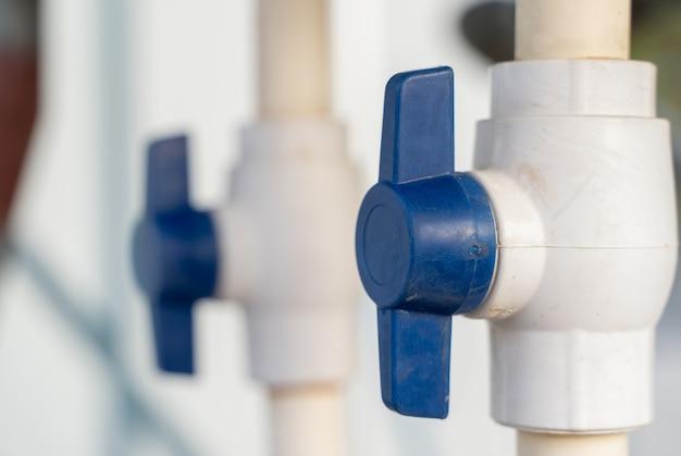 파란색 수도꼭지가 있는 흰색 플라스틱 수도관, 가정용 급수 시스템의 일부, 클로즈업 스톡 사진