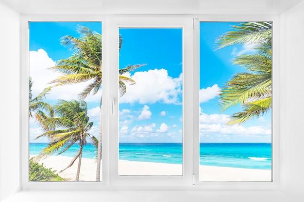 海と青い空のそばのヤシの木とビーチの美しい景色を望む白いプラスチックの窓。熱帯の島の窓からの美しい景色とホテルからの自然。