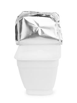白い背景で隔離の蓋付きの白いプラスチック製ヨーグルト牛乳瓶