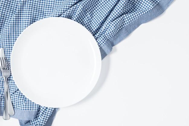 화이트 플레이트와 체크 무늬 블루 식탁보 평평하다