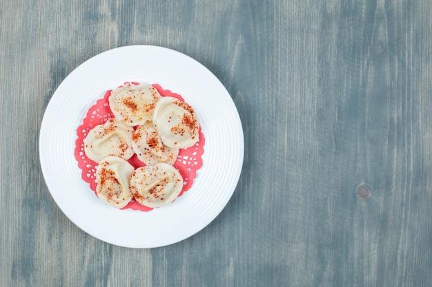 Piatto bianco di gnocchi di carne bollita su superficie di legno.